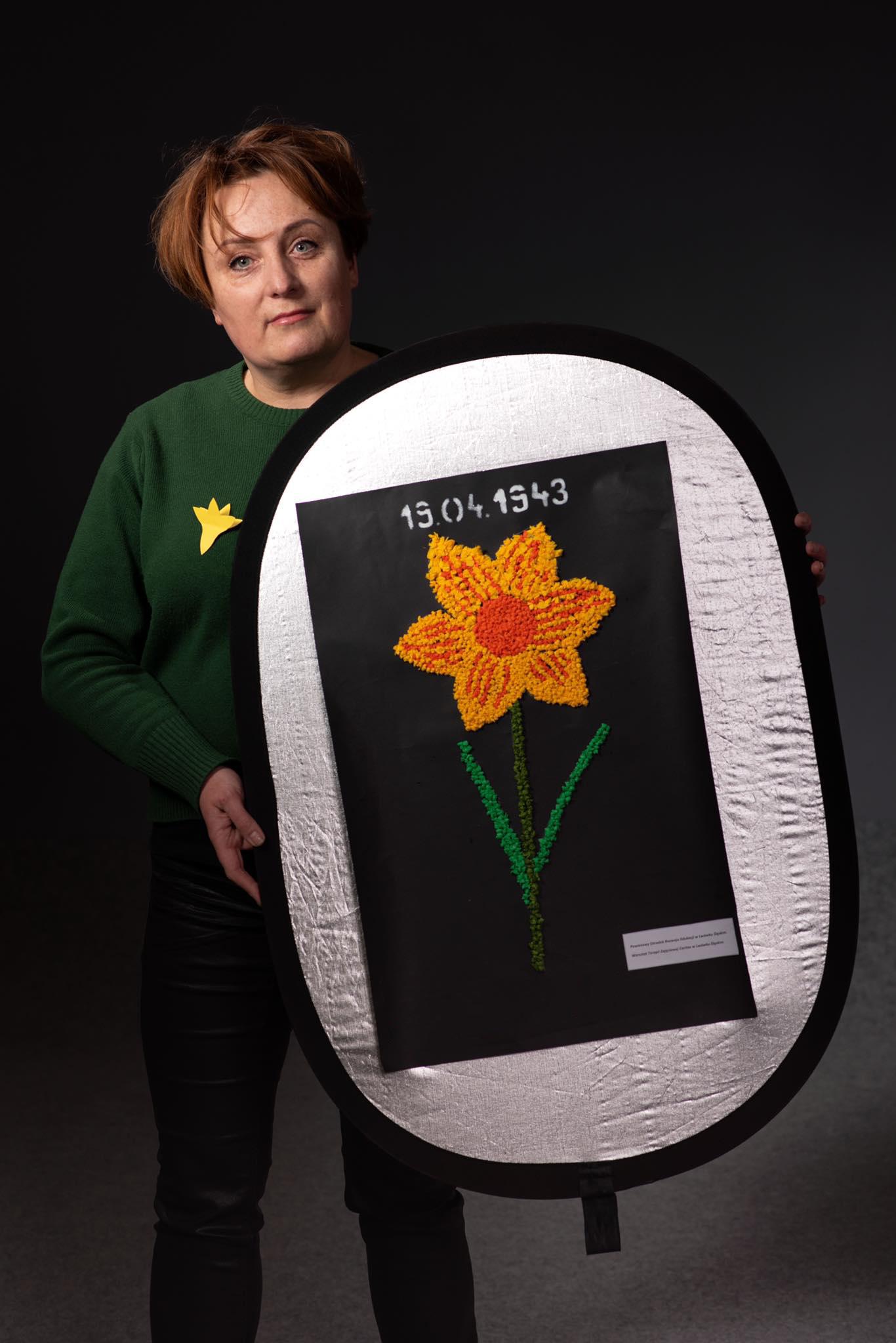 """Przewodnicząca Rady Powiatu Małgorzata Szczepańska trzyma przed sobą plakat jednego z uczestników akcji """"Łączy nas pamięć"""" - na obrazie żonkil"""