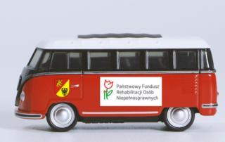 na zdjeciu zabawkowy autobus stylizowany na lata 60-te z logotypami PFRON i Powiatu Lwóweckiego